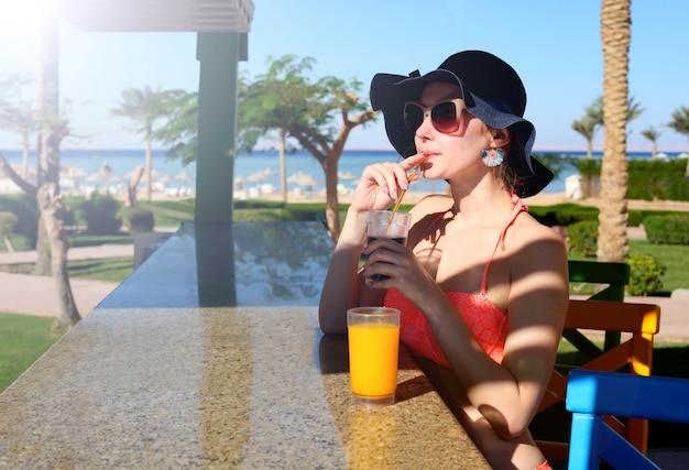 Beautiful sexy women in bikini in bar on hawaii beach bar. enjoying alcoholic beverage cocktail outside. smiling happy caucasian women in a hat on hawaiian beach.