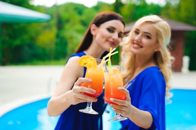 スイミングプールでリラックスしながらカクテルを飲んでビキニで美しいセクシーな女性
