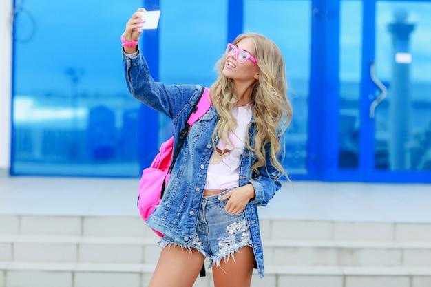 長いウェーブのかかった髪の美しいセクシーな若いブロンドの女性は、ほっそりした体型の完璧なボディとビンテージスーツとブルージーンズのジャケットを着てきれいな顔のメイク。夏のアクセサリー、ピンクのバックパック