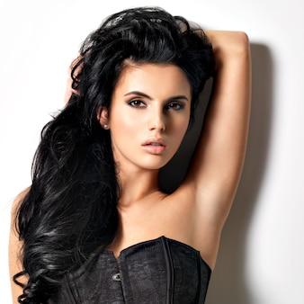 Bella giovane donna castana sexy con capelli lunghi. ritratto di una bella modella in posa.