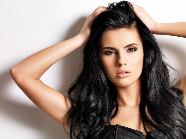 Красивая сексуальная молодая женщина брюнет с длинными волосами.