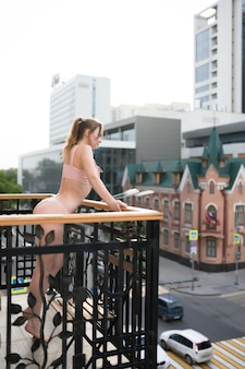 A beautiful, sexy, young girl in pink underwear stands on the balcony. relaxation and enjoyment concept