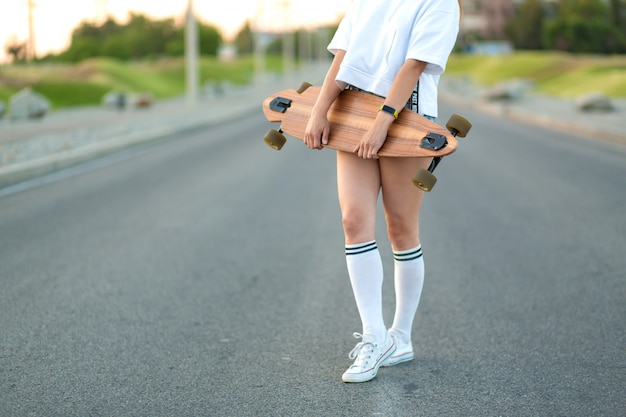 Beautiful sexy young girl in short shorts walking with longboard in sunny weather. leisure. healthy lifestyle. extreme sports. fashion look, outdoor hipster portrait, bali, sneakers,hipster,sunse