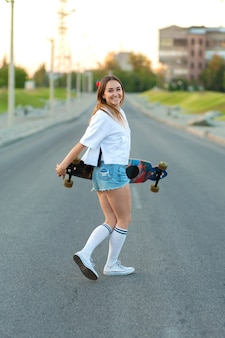 Beautiful sexy young girl in short shorts walking with longboard in sunny weather