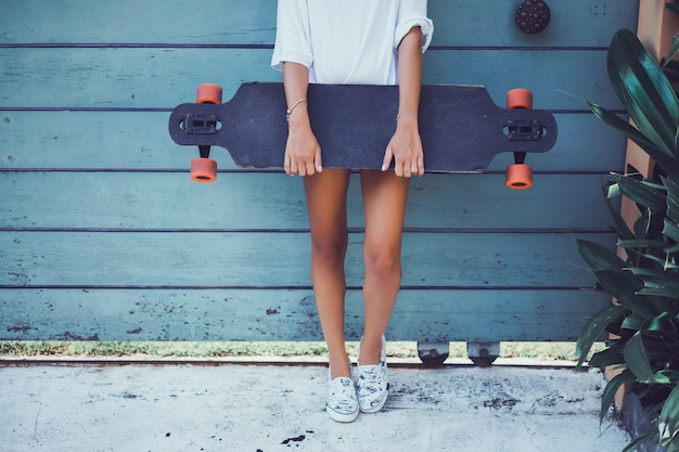 Beautiful sexy young girl in shorts with longboard in sunny weather