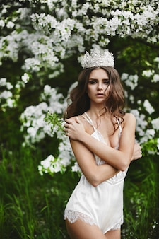 Beautiful and sexy young model woman with perfect body in stylish lingerie with the crown on her head posing under the blossoming tree at green forest
