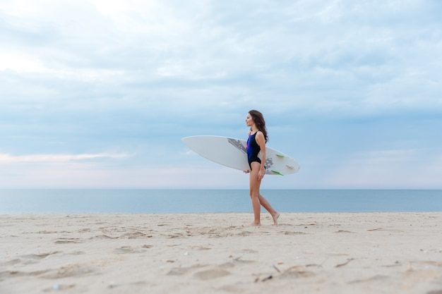 Beautiful sexy young surfer girl walking on the beach