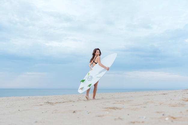Красивая сексуальная молодая серфер девушка гуляет на пляже