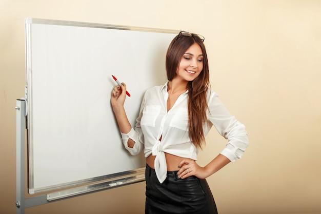 マーカーを保持し、ホワイトボードに書き込む美しいセクシーな若い女性
