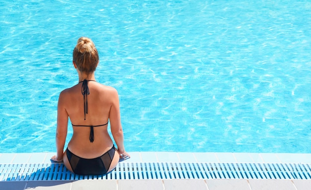 プールの棚に座っている美しいセクシーな若い女性。
