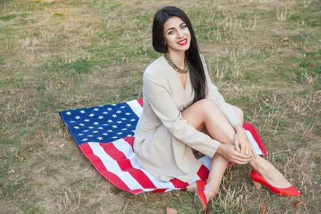 Красивая сексуальная молодая женщина с классическим платьем, лежа на американском флаге в парке. фотомодель держит нас улыбается и смотрит в камеру. образ жизни сша с зубастой улыбкой.