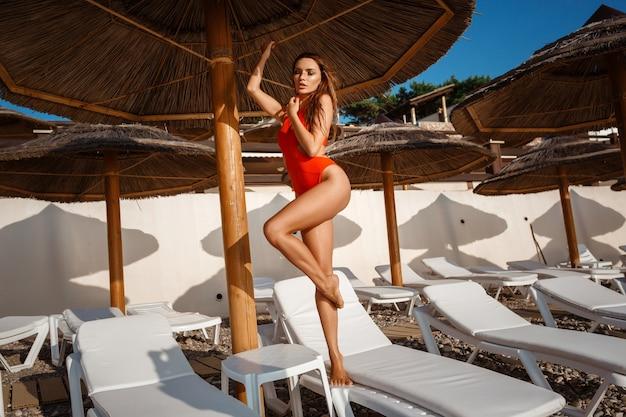 長い黒髪と濡れた水着のファッションで太陽からのスタイリッシュな水着で完璧なスリムな体型の美しいセクシーな若い女性は、スイミングプールで日光浴をしています