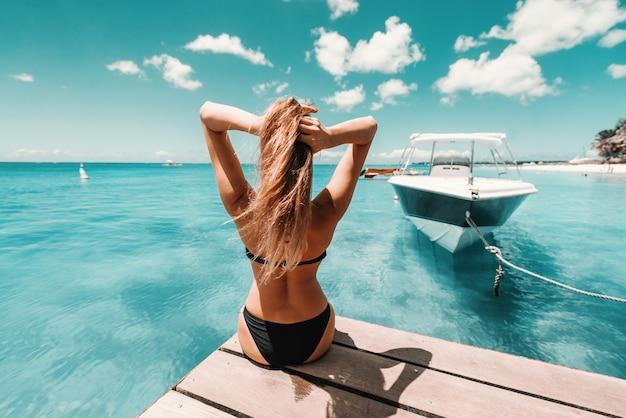 Брюнетка красивой формы в купальнике с солнцезащитными очками сидит на пирсе и наслаждается солнечной погодой и океаном. обратно повернулся.