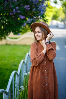 Красивая стройная длинноволосая девушка в шляпе на фоне цветов сирени