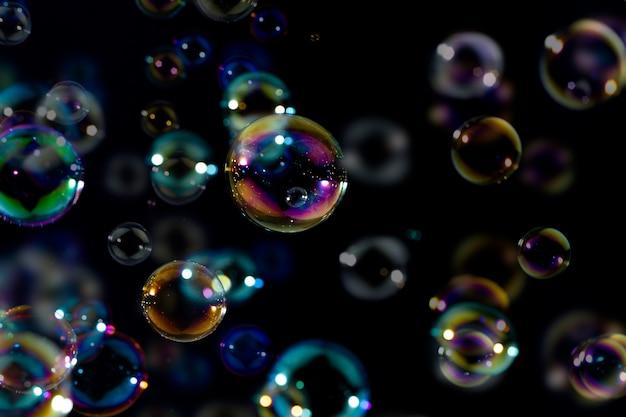 Красивые блестящие красочные мыльные пузыри, плавающие в темноте. абстрактный, естественный свежий летний фон.