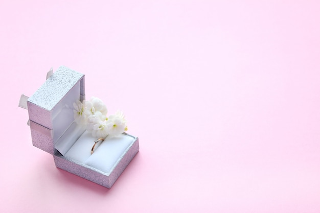 Beautiful shiny gold engagement ring with gem diamond in gray box and white flowers on pink background