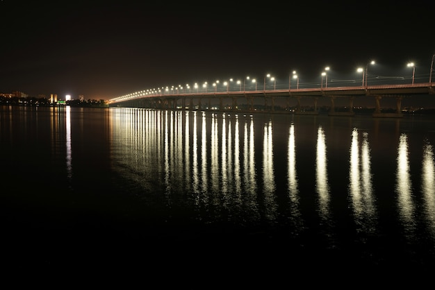 Beautiful shiny reflection of bright lanterns with cold light in the big dnieper river under a long bridge passing over it