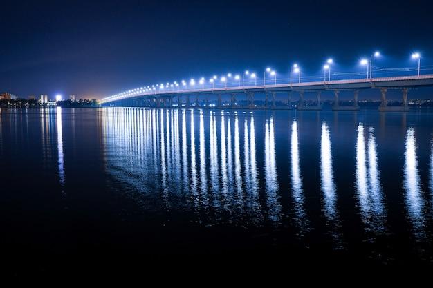 긴 다리 아래 큰 드니프르 강에서 차가운 빛으로 밝은 등불의 아름다운 반짝이는 반사
