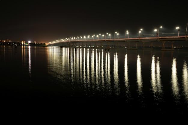 Красивое блестящее отражение ярких фонарей с холодным светом в большой реке днепр под проходящим над ней длинным мостом
