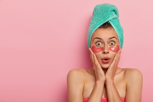 Beautiful shocked lady touches cheeks with both hands, has stupefied look, applies collagen pink patches for reducing fine lines under eyes, has wet hair wrapped in towel, models indoor