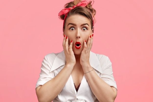 Красивая шокированная женщина кинозвезды, одетая в одежду в стиле ретро, накрашена, трогает щеки ладонями, держит челюсть отвисшей от чуда