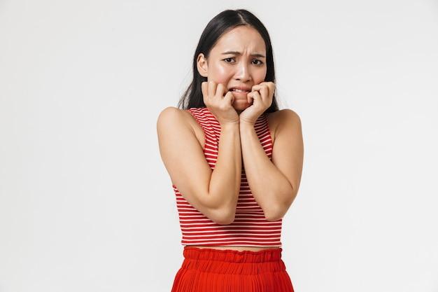 아름다운 충격을 받은 겁 먹은 젊은 예쁜 아시아 여성이 흰 벽에 격리된 채 포즈를 취했습니다.