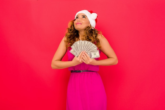 A beautiful shocked sexy girl in a new years hat hold in hands money