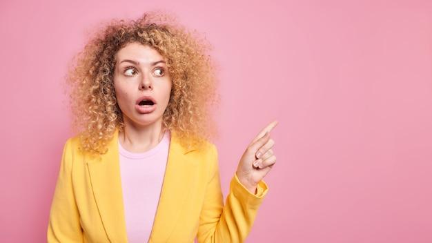 ふさふさした巻き毛を持つ美しいショックを受けた女性は、予期しない販売オファーに驚いた驚くべきオファーを示し、ピンクの壁に黄色い服を着ていることを示していますうわあそこ見て