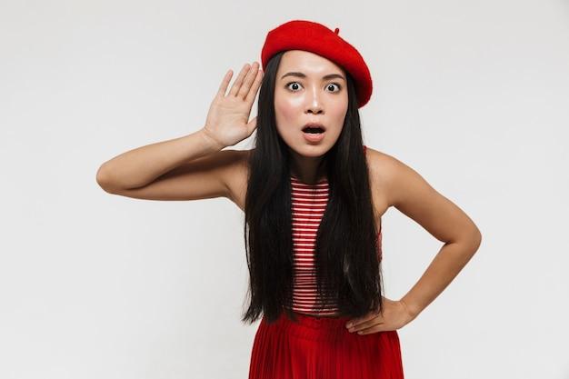 何かを聞いて白い壁の上に孤立してポーズをとってポーズをとる美しいショックを受けた若いかなりアジアの女性。