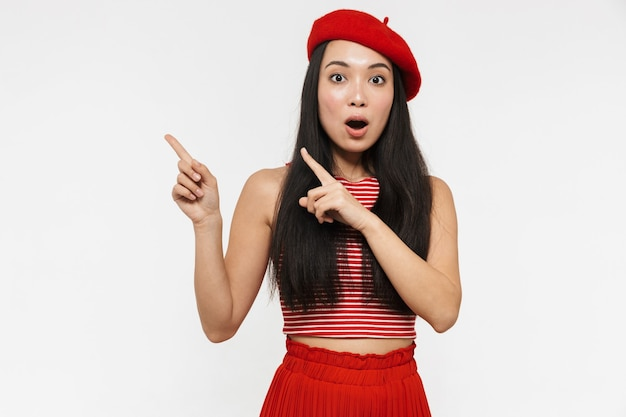 Beautiful shocked young pretty asian woman posing isolated over white wall pointing.