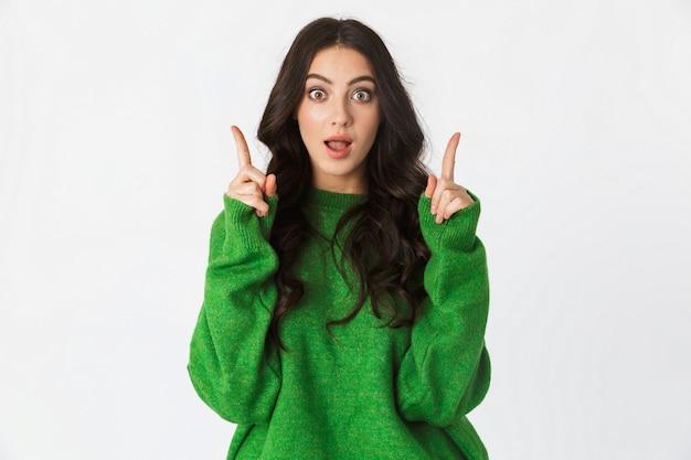 白い壁のポインティングで隔離のポーズをとる緑のセーターに身を包んだ美しいショックを受けた若い女性はアイデアを持っています。