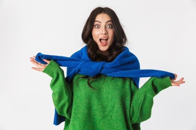 白い壁に隔離されたポーズの緑のセーターに身を包んだ美しいショックを受けた若い女性。