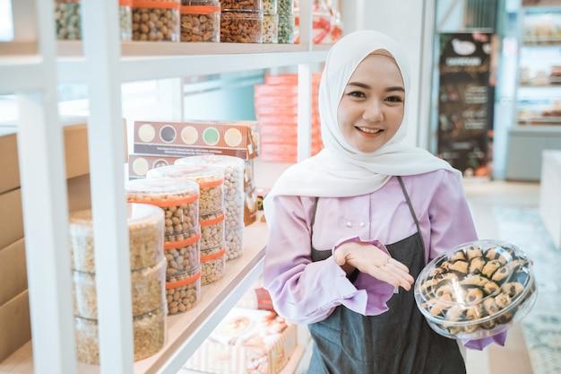 彼女の店でイードムバラクのケーキを持っている美しい店主のイスラム教徒の女性