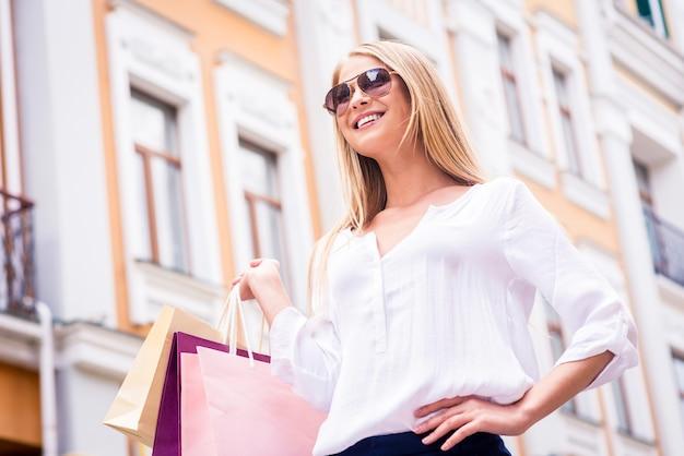 아름다운 쇼핑 중독자. 선글라스를 끼고 쇼핑백을 들고 야외에 서 있는 동안 멀리 바라보는 아름다운 젊은 금발 머리 여성의 낮은 각도