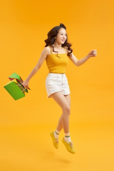 Красивая молодая женщина шопоголика прыгает в воздухе с хозяйственными сумками на оранжевом фоне.