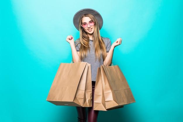 Красивая женщина покупок улыбается и носит шляпу, изолированные на зеленом фоне