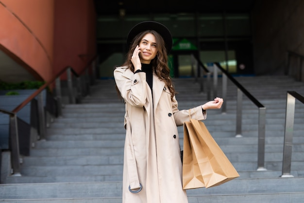 Красивая женщина покупок разговаривает по телефону в торговом центре