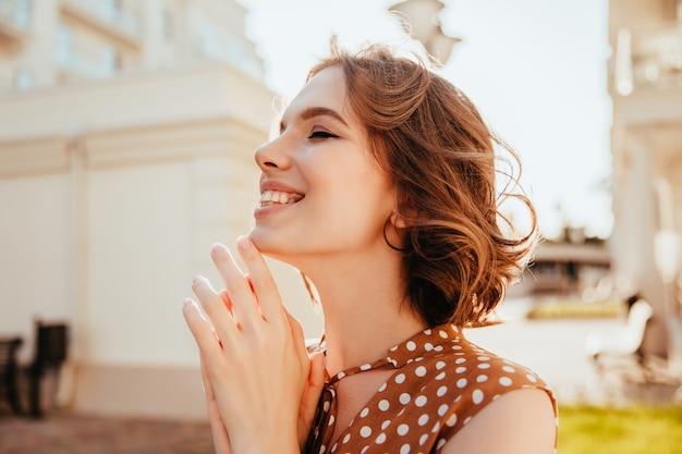 감정적으로 야외 포즈를 취하는 아름 다운 짧은 머리 소녀. 거리에 웃 고 화려한 갈색 머리 여성 모델입니다.