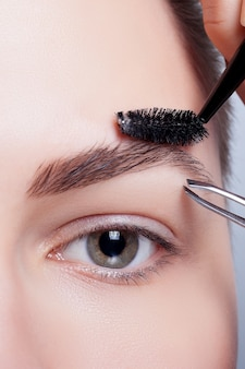 Красивая короткошерстная женщина с чистой кожей выщипывает брови