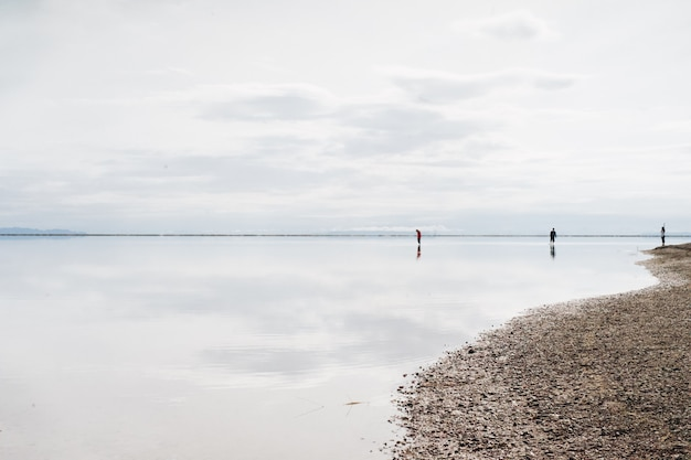 Beautiful shot of a beach with three people there on a cloudy day