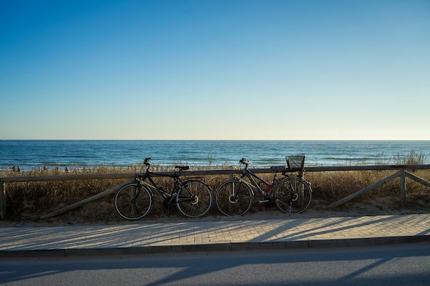 Beautiful shot of bicycles near an empty street with a sea on the background