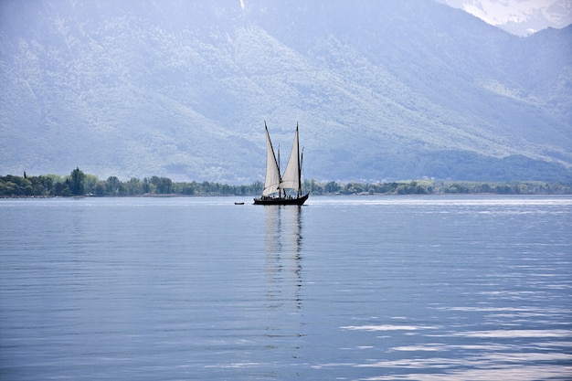 Beautiful shot of a boat sailing on the water with forested mountains