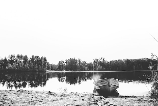 Beautiful shot of a boat on the water near the shore with trees in the distance in black and white