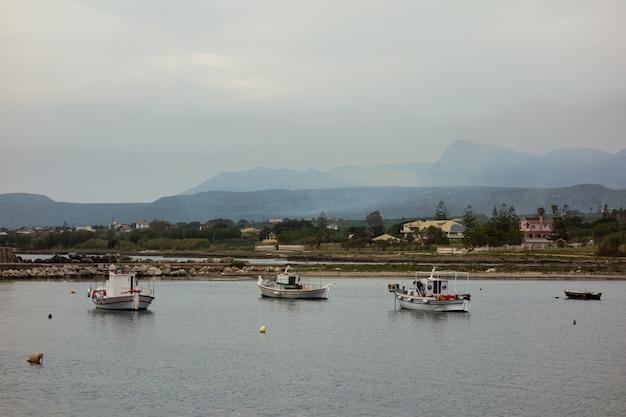 Bellissimo scatto di barche sull'acqua con edifici e montagne in lontananza