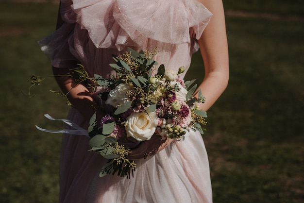 Beautiful shot of a bride wearing wedding dress holding a flower bouquet