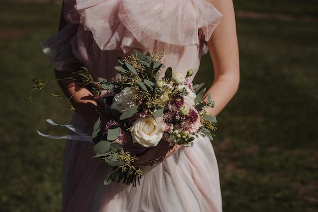 Bello colpo di un vestito da sposa d'uso da sposa che tiene un mazzo del fiore