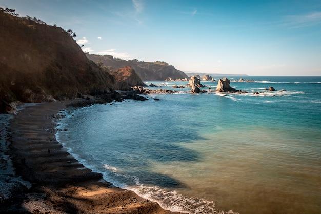 Bella ripresa di un mare calmo con colline sul lato sotto un cielo blu nelle asturie, in spagna