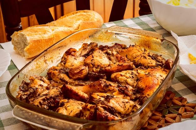 Bella ripresa di un pollo con salsa in padella e pane sul tavolo
