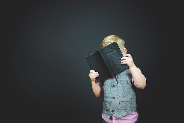 Beautiful shot of a child holding an open bible