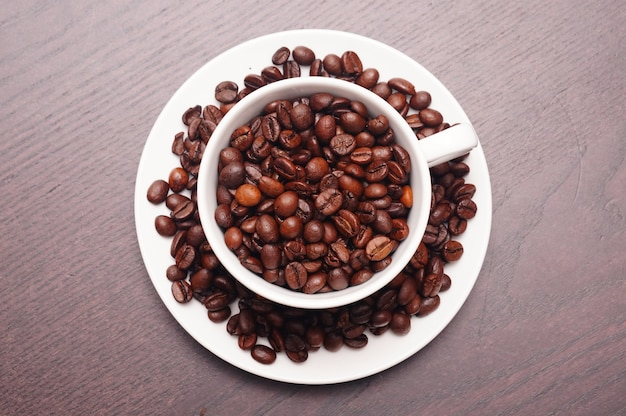 Beautiful shot of coffee beans in the white cup and plate on a wooden table
